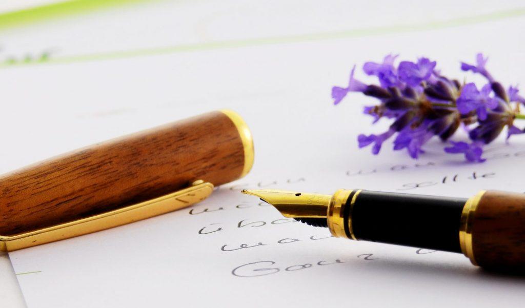 Billede af et brev og en fyldepen i træ, ved siden af ligger en lilla lavendel blomst