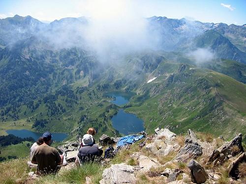 Mennesker sidde på en bjergtop og kigger ud over 3 bjergsøer