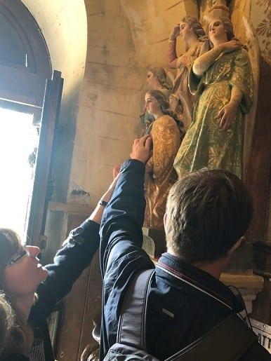 Cheri synstolker og beskriver detaljer, mens den blinde gæst føler på figuren i den gamle kirke.